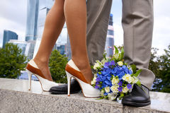 Legs of man and woman - bride and groom - and wedding bouquet of white and blue flowers Stock Photography