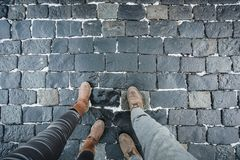 The legs of a man and a woman in leather shoes against the background of stone pavers laid out of stone. royalty free stock images