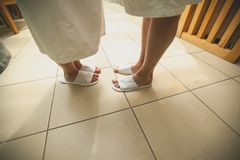 Legs of a man and a woman in swimming Slippers close-up. Young couple in bath robes and Slippers, standing on the tiled floor stock photo