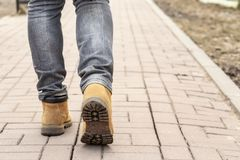 The legs of a man in yellow boots on a paved stone roadway on a Stock Images
