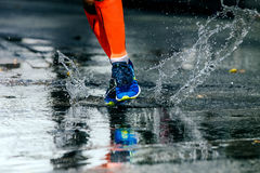 Legs men in marathon compression socks. Running through a puddle, water sprays Stock Photos