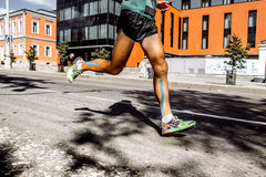 Legs men marathon with taping on calf muscles. Running on a city street Stock Photography