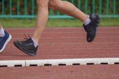 Legs of men running in the running track. stock photo