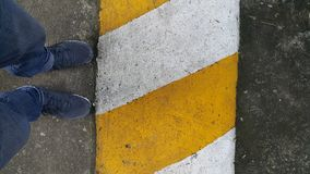 Legs of men are walking on the white-yellow line. Legs of men are walking on the white-yellow line, warning to be careful in driving royalty free stock image