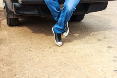 Legs men wearing black sneakers. Sitting behind a pickup.  Stock Photo