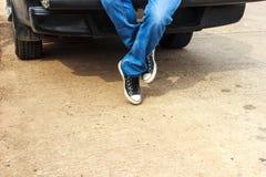 Legs men wearing black sneakers. Sitting behind a pickup Stock Photo