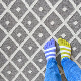 Legs in mismatched socks on gray carpet royalty free stock photography