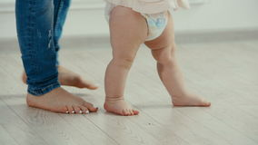 Legs of mother and baby. The baby`s first steps stock footage