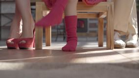 Legs of the mother, little daughter and grandmother. Woman has red shoes, girl stockings and granny beige sandals on. Their feet stock footage