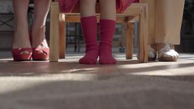 Legs of the mother, little daughter and grandmother. Woman has red shoes, girl stockings and granny beige sandals on. Their feet. Child sitting on the table stock video footage