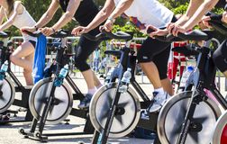 Legs moving during a workout of spinning. Imperia, IM, Italy - May 18, 2014: People perform a spinning session outdoors in an urban park of liguria. Athlets Stock Images