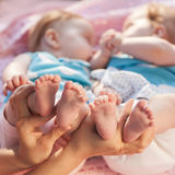Legs newborns in parents hand. Twins lying on a pink blanket Royalty Free Stock Image