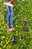 Legs and notebook with yellow dandelion Royalty Free Stock Photo