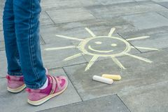 Free Legs Of Child With Painted Symbol Of The Sun Colored Crayons On The Asphalt Stock Image - 127459781