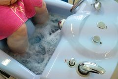 Legs of the old man or woman in the air bath. Foot treatment. Varicose veins in adults royalty free stock images