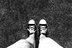 Legs in old sneakers on grass. View from above. Style: abstraction, illustration, monochrome, neon.  stock images