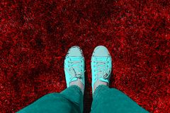 Legs in old sneakers on grass. View from above. Style: abstraction, illustration, monochrome, neon.  stock photos