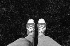 Legs in old sneakers on grass. View from above. Style: abstraction, illustration, monochrome, neon royalty free stock images