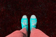 Legs in old sneakers on grass. View from above. Style: abstraction, illustration, monochrome, neon stock photography