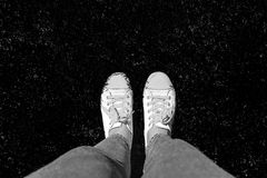 Legs in old sneakers on grass. View from above. Style: abstraction, illustration, monochrome, neon stock photos