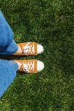 Legs in old yellow sneakers on green grass. View from above. The stock photos