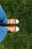 Legs in old yellow sneakers on green grass. View from above. The stock photography