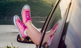 Legs out of the car window by the lake royalty free stock images