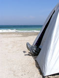 Legs out of the tent. On the seashore stock image