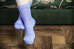 Legs overhang from the sofa in purple socks Royalty Free Stock Image