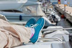 Legs in pants and bright blue topsiders on yacht Stock Photos