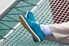 Legs in pants and bright blue topsiders on yacht Stock Images