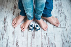 Legs of parents with children`s sneakers. Waiting for the baby. Royalty Free Stock Photography