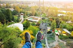The legs of the passenger and the view down to the ground. Cable car in the summer park. Open seats for transportation. Of tourists Royalty Free Stock Photo