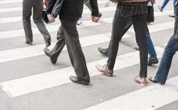Legs of pedestrians in a crosswalk Stock Images