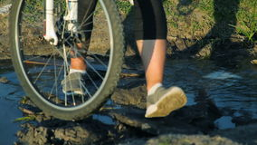 Legs of people crossing a stream with their bikes stock video footage
