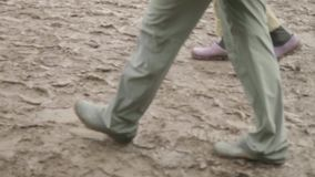 Legs of people in rubber boots walking in mud after rain. Slow motion stock video