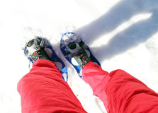 Legs of People while snowshoeing in the mountains Stock Image