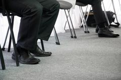 Legs of people waiting for their turn on office chairs in the hallway. Interview and job search stock image