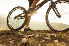 Legs of person on bike. Horizontal outdoors shot of legs of sportsman on a trial bicycle treadle. Horizontal outdoors shot Royalty Free Stock Photo