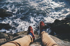 Legs of person on cliff overlooking sea