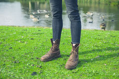 Legs of person by pond with birds Royalty Free Stock Photos