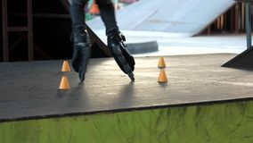Legs of person on rollerblades. Rollerblader and slalom cones, motion stock video footage