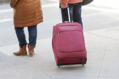 Legs of the person rolling a tourist bag on wheels Stock Photography
