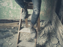 Legs of person sitting on stepladder Stock Image