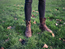 Legs of person standing on the grass Stock Photo