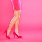 Legs and pink high heels shoes. Closeup of woman legs and shoes on pink background royalty free stock images