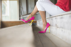 Legs and pink high heels sitting relaxed. Concept close up image of woman sitting in Elegant sexy pink high heel shoes, sitting relaxed on bench, copy space Royalty Free Stock Photos