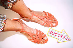 Legs in pink sandals walking on to success Royalty Free Stock Photo