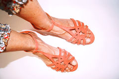 Legs in pink sandals walking on white background Royalty Free Stock Image