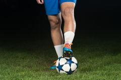 Legs Of Player With Ball On Dark Background Royalty Free Stock Image